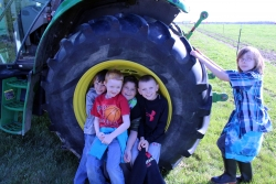 School children pose in tractor wheel