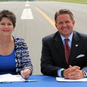 Adkins and Benson sign agreement on the runway