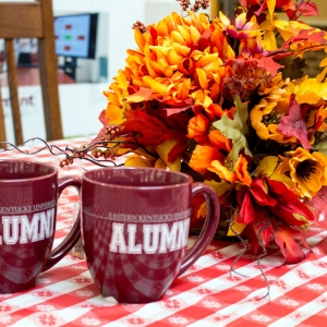 EKU alumni mugs on fall decorated table